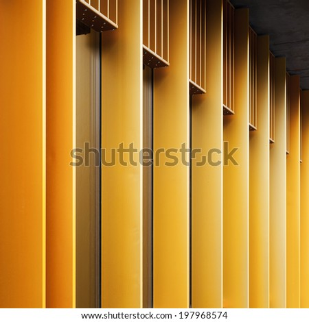 Abstract architecture fragment with yellow metal facade and windows - stock photo