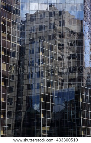 Abstract architecture. Reflected architecture. Glass surface of skyscrapers view in district of business centers with reflection. Multiexposition. Blue sky reflected in windows. Montreal.