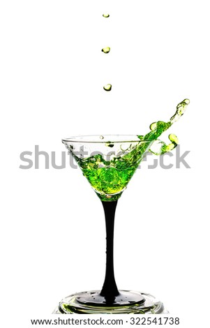 Abstract art. Cocktail glass with splashes of liquid isolated on a white background. Alcoholic cocktail. Quench your thirst. Cocktail party.