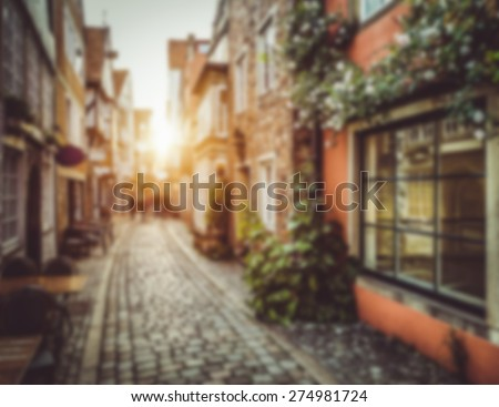Abstract background blur bokeh image of an old town in Europe in beautiful golden evening light at sunset with pastel toned retro vintage Instagram style filter and lens flare effect - stock photo