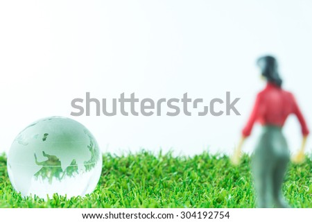 Abstract Background : Blur Miniature Business Woman Looking To Glass Earth On Green Artificial Grass - stock photo