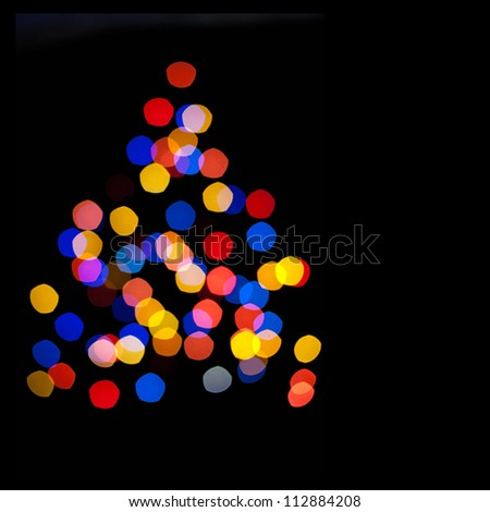 Abstract background - blurred colorful circles bokeh of Christmaslight in the form of a Christmas tree against dark background - stock photo