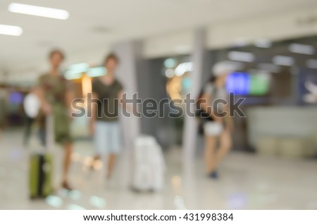 Abstract background,  blurred  image of passengers with baggage walking in corridor of passenger terminal at the airport. - stock photo