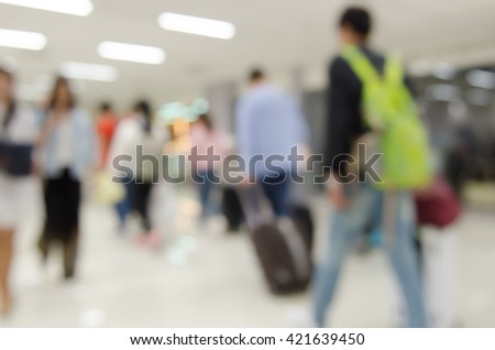 Abstract background,  blurred  image of people with baggage walking in corridor of passenger terminal at the airport. - stock photo