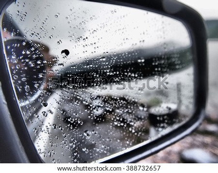 Abstract background, De-focused rain drops on the wing mirror. Very shallow depth of field. Selective focus.