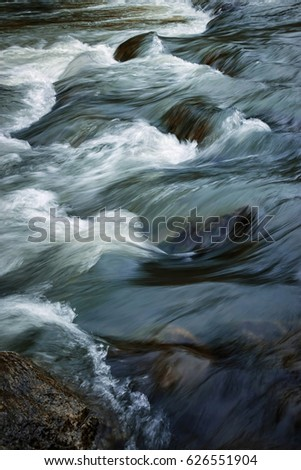 abstract background Detail of a river with a stone in the foreground