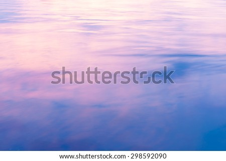 Abstract background light on water as colors of clouds at sunset reflect with pink transitioning to blue in the surface ripples.
