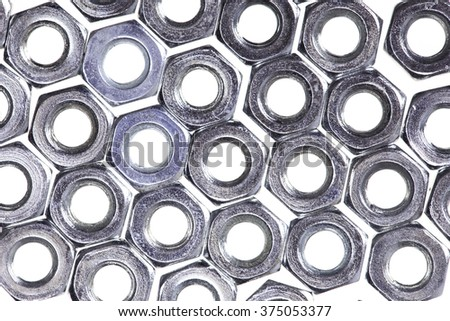 abstract background lot of metal nuts closeup isolated on white