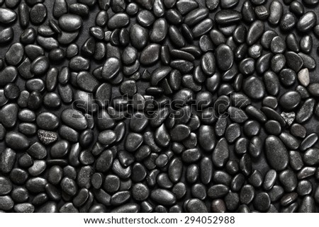 Abstract background of black pebble stones arranged on black surface - stock photo