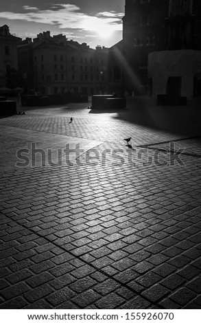 Abstract background of cobble stone road. Early morning shadows in old Krakow - stock photo