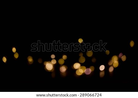 Abstract background of gold bokeh on a black background.