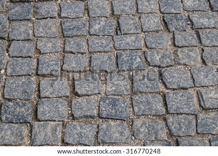 Abstract background of old cobblestone pavement close-up - stock photo