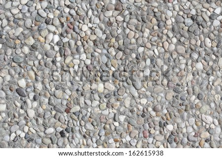 Abstract background paving consisting of small pebbles embedded in cement - stock photo