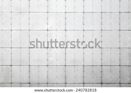 Abstract background photo texture of gray metal wall with tiles and rivets - stock photo