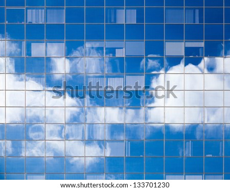 Abstract background texture with bright clouds reflected in windows of modern office building - stock photo