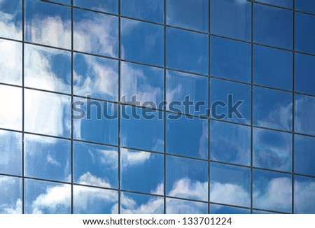 Abstract background texture with clouds reflected in windows of modern office building - stock photo