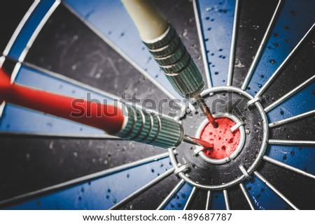 Abstract background to target marketing concept: target dart with arrow over wooden background.