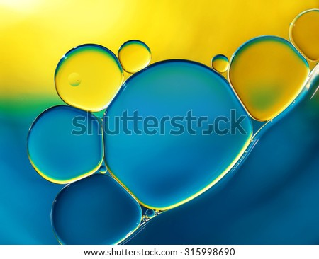 Abstract background with oil drops on water, yellow and blue macro. - stock photo