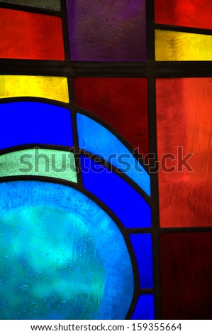 Abstract backlit stained glass window detail with primary colors and shapes - stock photo