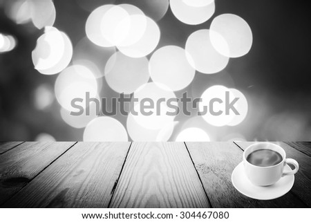 Abstract black and white bokeh of light and coffee cup and wood background - stock photo