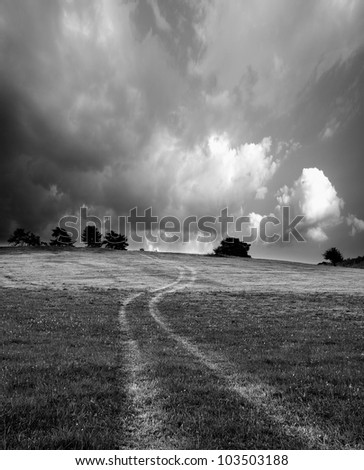 abstract black and white landscape with country road in meadow - stock photo