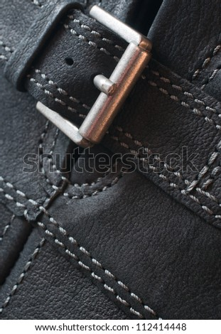 Abstract black leather background with seams and buckle - stock photo