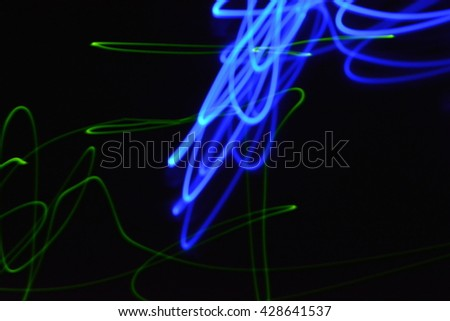 Abstract blue and green streaks of light on a black dark background creates a unique pattern.