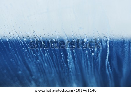 Abstract blue foam running down the glass. Shallow depth of field. - stock photo