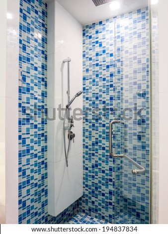 Abstract blue glass mosaic with shower faucet in bathroom - stock photo
