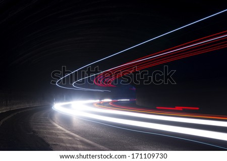 Abstract blue, red and white rays of light in a car tunnel