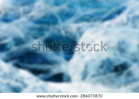 Abstract Blue river ice with large cracks. Deep blur. - stock photo