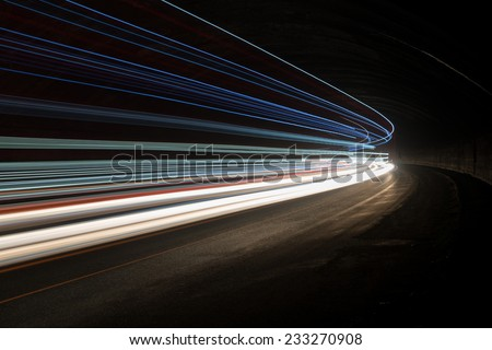 Abstract blue, yellow and white rays of light in a car tunnel - stock photo