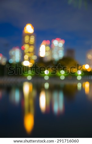 Abstract blur bokeh city lights during twilight, with water reflection - stock photo