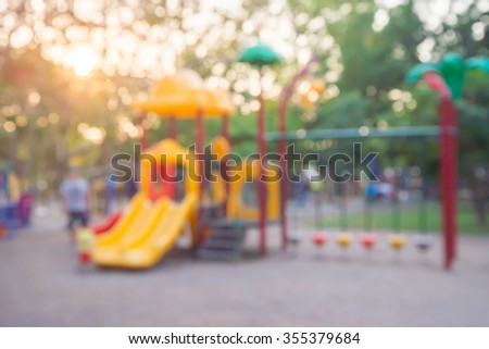 Abstract blur children playground in city park with warm evening sunlight background - stock photo