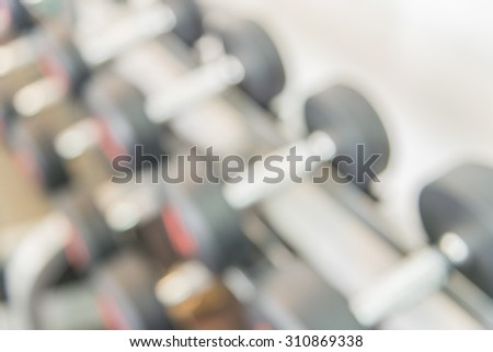 Abstract Blur dumbbells in gym background - stock photo