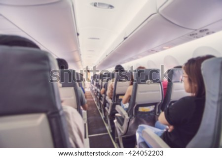 Abstract blur Interior of airplane with passengers on seats waiting to taik off.