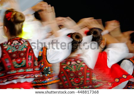 Abstract blur moving with amazing dance. Young Romanian dancers in traditional costume. - stock photo