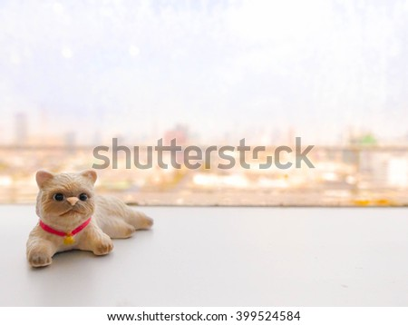 Abstract Blur of a cityscape with miniature of a cat on the foreground, copy scape or for background. Selective focus on the cat's eyes (Pet in a city concept) - stock photo