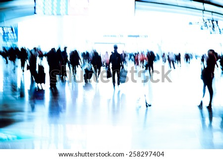 abstract blur of passengers rushing at big city station.