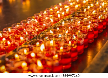 Abstract blur of red candles is kindle a fire in glass at the Chinese temple, Prayers for Chinese new year.