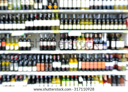 Abstract Blur or Defocus Background of Bottles of Wine on Shelf in Supermarket or Liquor store. - stock photo