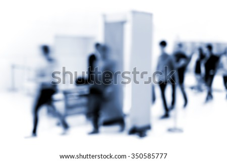 Abstract blur people walking through security gate entering building in black and white
