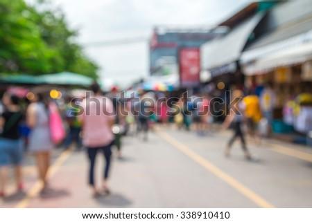 Abstract blur tourist shopping in Chatuchak weekend market outdoor in sunny day Bangkok Thailand background