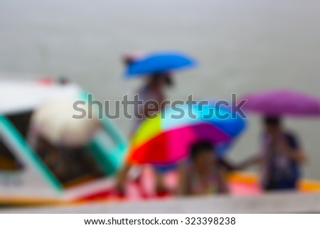 Abstract blur tourists use umbrellas while up from the boat landing dock, and while it is raining heavily. - stock photo