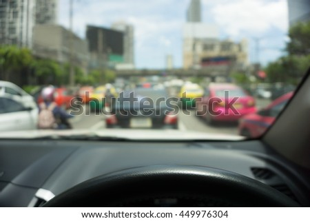 Abstract blur traffic from inside car view background, Selective focus on steering wheel - stock photo