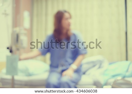 abstract blurred asian woman patient sit on bed at hospital:healthcare medical concept.blurry sickness girl with saline drilling intravenous medical equipment:weakness illness people:vintage effect - stock photo