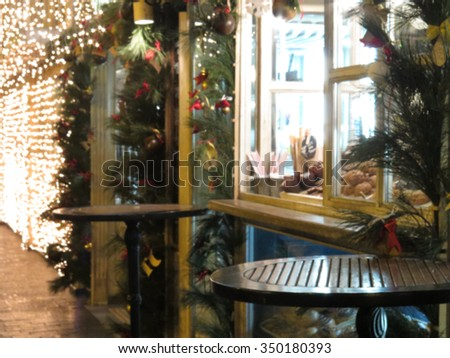 Abstract blurred background: Christmas decorations and Christmas tree in the windows of the town's shops and cafes with blur bokeh. Great Christmas background.