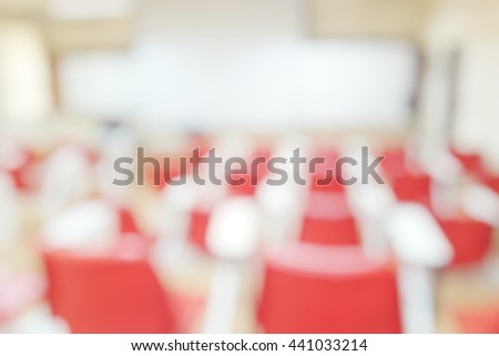 Abstract blurred background image of empty classroom without student after school; Blurry view of nobody lecture room with red armchairs and projector whiteboard. - stock photo