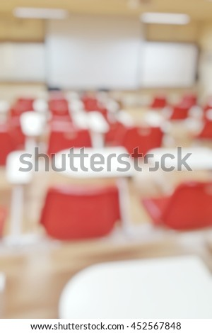 Abstract blurred background image of empty classroom without student after school;Blurry view of exam hall with chairs and tables in room at the end of semester in college or university.Back to school - stock photo