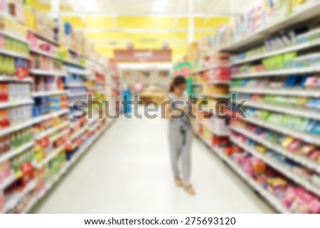 Abstract blurred background of a female customer shopping in a supermarket                                - stock photo